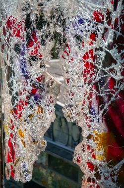 Broken glass windows in an old abandoned building or factory, completely destroyed and vandalized, painted with colourful graffiti street art