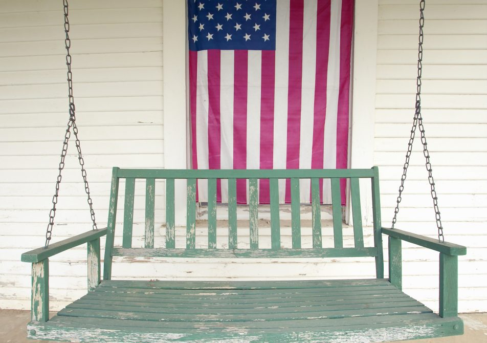 Old swing on porch displaying an American Flag and patriotic theme near Barstow CA off Route 59
